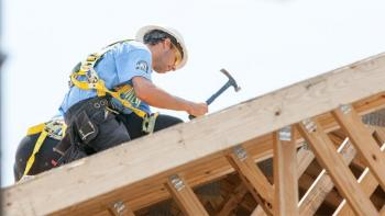 AmeriCorps volunteer hammering on roof