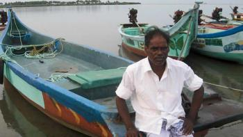 G. Sundaramurthy leaning on his fishing boat
