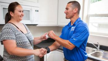 Homeowner receives key from volunteer builder