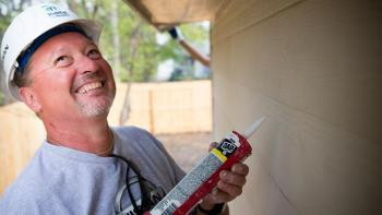 Habitat for Humanity U.S. volunteer caulking a home