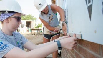 Volunteers measuring insulation on a build site