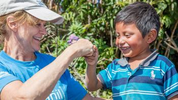 Woman volunteer fist bumping with kid in Guatemala on Global Village trip site.