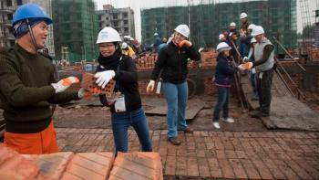 Volunteers laying bricks in China