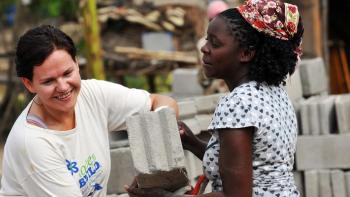 Photo: Volunteer building a wall of a house together with the future homeowner