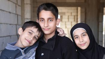 siblings from Syria living in Lebanon - two boys and a smiling girl wearing black scarf, new brick wall in the background