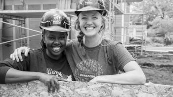 Two smiling volunteers in hard hats on a Habitat build site.