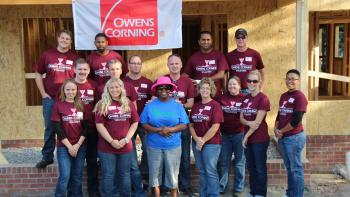 Group of Owens Corning volunteers stand with homeowner on a build site.