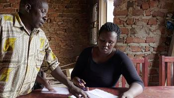 a woman from Uganda sitting at the table. She is studying her microloan payments book.