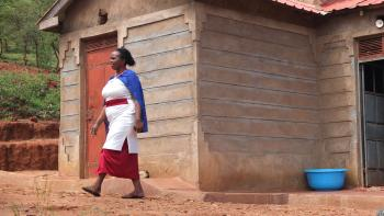 a woman walking in front of her house in Kenya