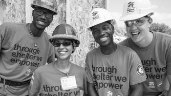 Diverse set of smiling volunteers on build site.