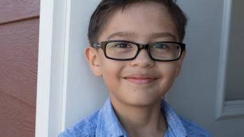 Smiling young boy with glasses