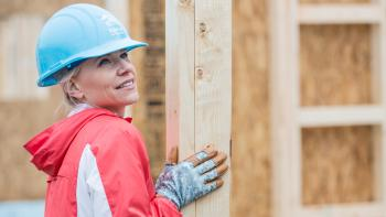 Woman in hard hat on build site