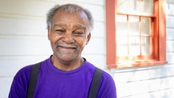 Walter stands on the front porch of his home, renovated with help from Habitat for Humanity