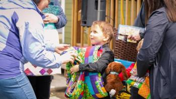 Little boy receives quilt.