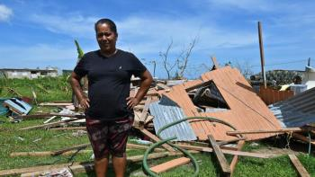 homeowner standing among hurricane aftermath in Puerto Rico.