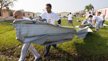 volunteers cleaning up hurricane debris.