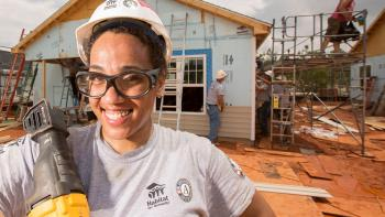 Smiling woman in front of house being built.