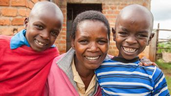 photo: a woman and two boys in front of a new house, Kenya