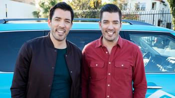Jonathan and Drew Scott stand in front of a car.