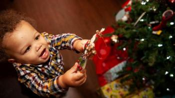 Little boy hangs ornament on Christmas tree.