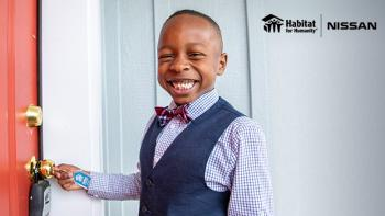 Smiling boy in bow tie unlocking door