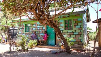 colorful house in Kenya surrounded by trees build with help of micro loans