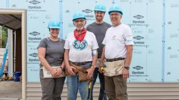 Stoesz family stands together on the build site.
