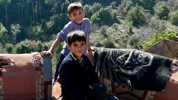 Photo: two boys sitting on an old sofa outside. Mountains in the background.