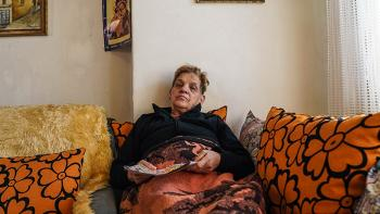 Photo: a woman from Skopje wrapped in a blanked sitting on a sofa and reading a magazine