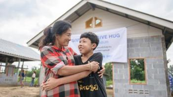Mother and son hugging in front of house