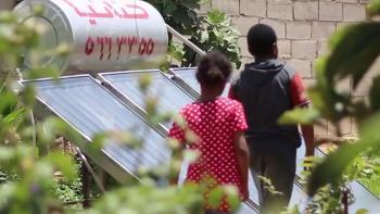 Photo: two children walking in green garden with solar panels