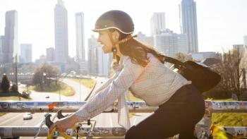 Woman riding bike in city smiling.