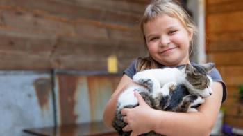 Miroslaw's daughter holding their pet cat.