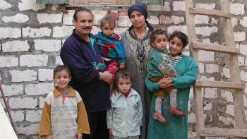 Photo: a family with 5 children, a new wall of their future house in the background