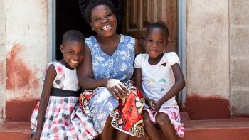 Photo: a women and two children from Zambia sitting on stairs in front of their house