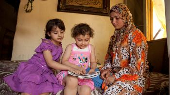 Inside a flat in Lebanon - two girls and their mother reading a book together