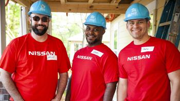 Three men in Nissan shirts smiling on build site.