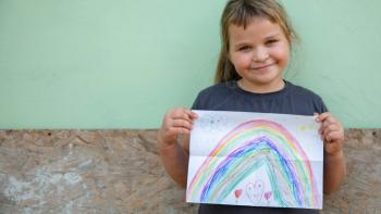 Little girl holds a drawing of a rainbow.
