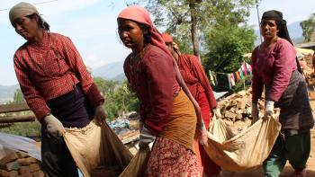 Photo: women carrying bricks together in a rug