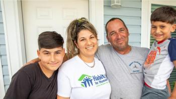 Parents with two sons smiling in front of house.