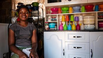 Photo: Lucy in her kitchen. Colorful dishes tidied up in the cupboard behind her.