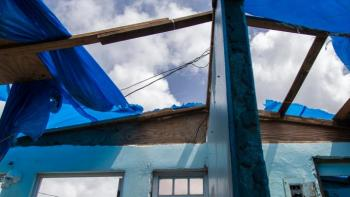 View from inside hurricane-damaged house of missing roof with blue tarps partially covering.