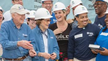 President and Mrs. Carter smiling with a group of Habitat volunteers and a Habitat homeowner.