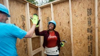 Homeowner high-fives a volunteer.