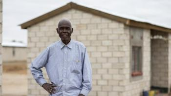 Zambian homeowner Jonathan in front of his home.