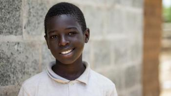 young Zambian boy smiling in front of his Habitat home.