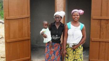 Photo: Two women and a child in front of a newly constructed latrine