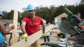 Man in a Wells Fargo volunteers shirt working on Habitat build site.