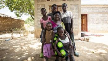 The Musonda family in front of their new home in Zambia built with the support of Habitat International and achieved through the Solid Ground Campaign.