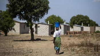 Margaret carries water from the nearby access point to her home built by Habitat Zambia, which feature concrete block construction and securely fastened roofs.